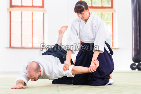 man and woman fighting at aikido
