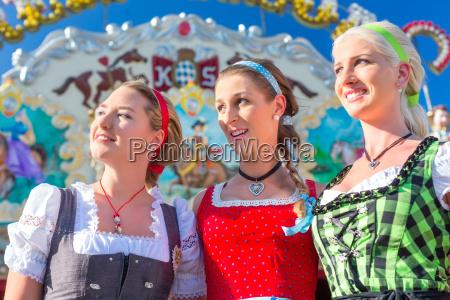 friends visiting bavarian fair having fun