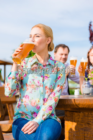 woman drinking with friends in beer