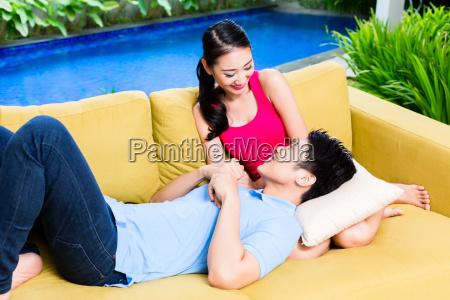asian couple huddling on sofa in