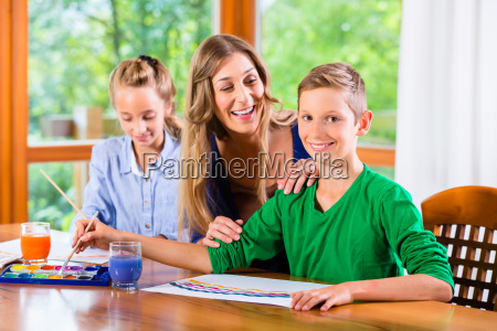 mother with kids painting pictures