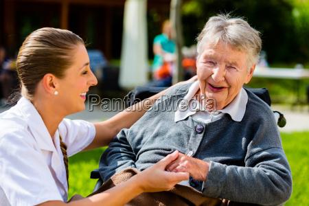 nurse holding hands with senior woman
