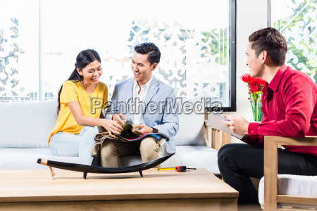 couple with shop assistant in furniture