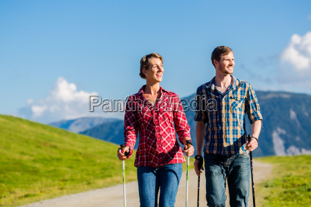 couple doing nordic walking exercise in