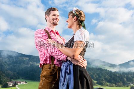 alpine cattle farmers on mountain meadow