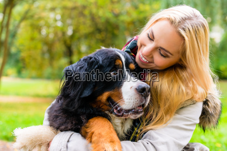 woman embracing her dog in autumn