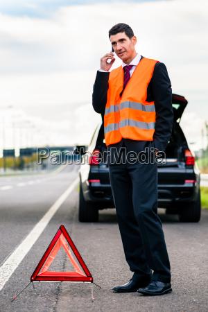 man with car breakdown erecting warning
