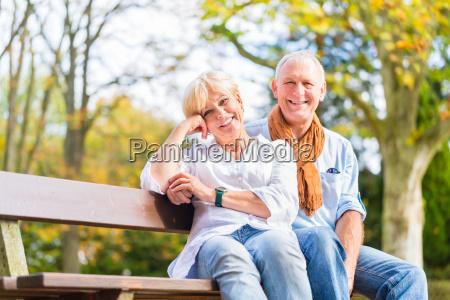 senior couple sitting on part bench