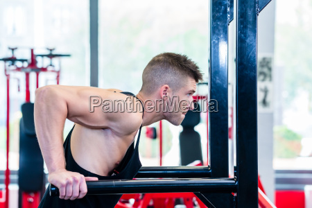 man training dips in fitness center