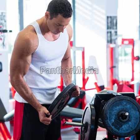 man taking weights from stand in