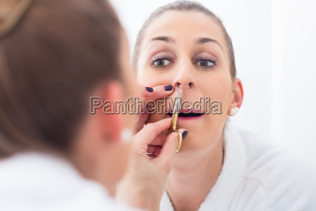 woman cutting her nostril hair