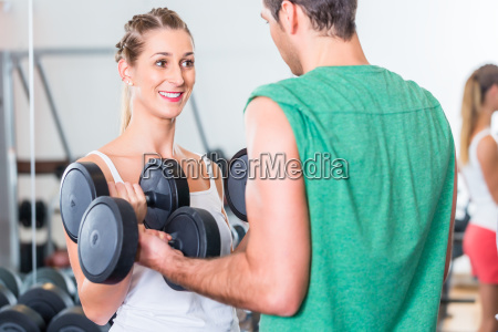 young couple in gym lifting dumbbell