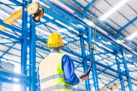 worker in factory controlling crane with