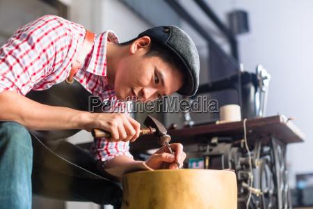 asian shoe or belt maker in