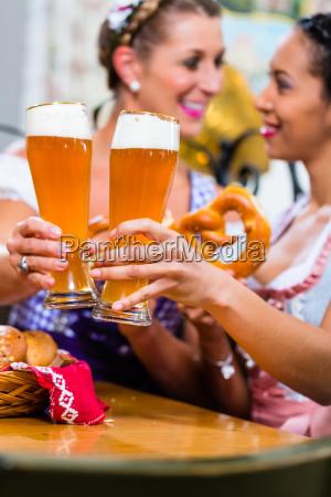 girlfriends with pretzel and beer in