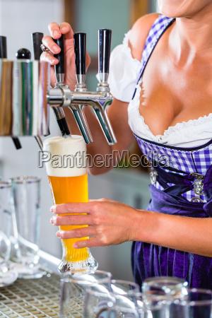 innkeeper in bavarian pub drawing beer