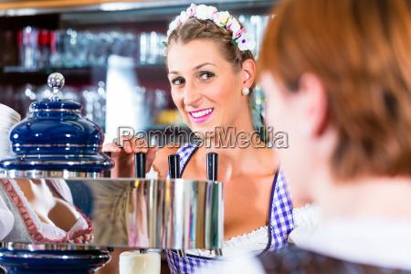 innkeeper in bavarian pub with customers