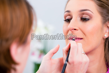 beautician applying lip color on woman