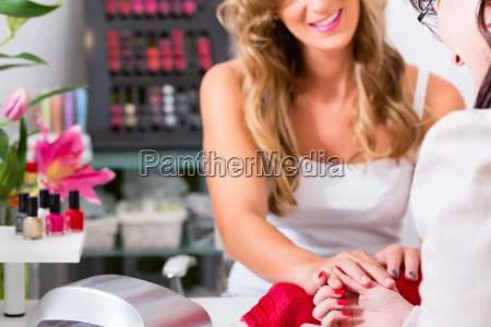 woman receiving manicure in nail salon