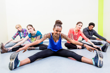 young people stretching legs in gymnastics