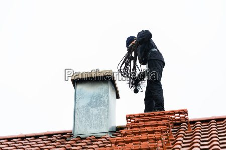 chimney sweep on roof of home