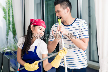 indonesian couple having fun cleaning the