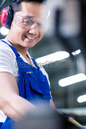asian worker operating metal skip in