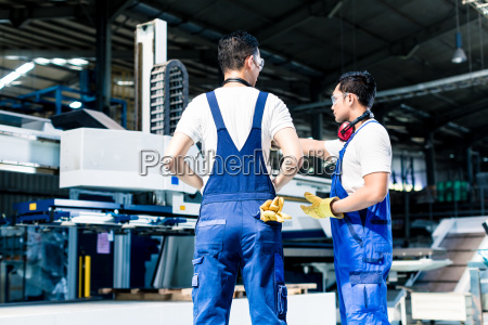 worker team in factory discussing in