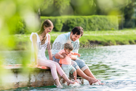 happy family sitting on jetty on