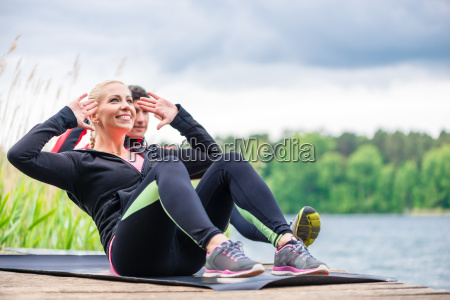 sport couple doing sit ups outdoor