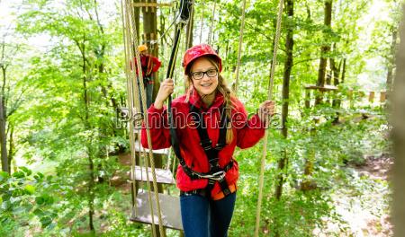 teenager girl climbing in high rope