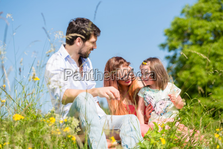 family playing with wildflowers on meadow