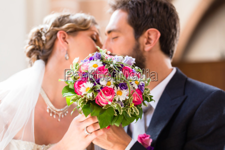 bridal couple giving kiss in church