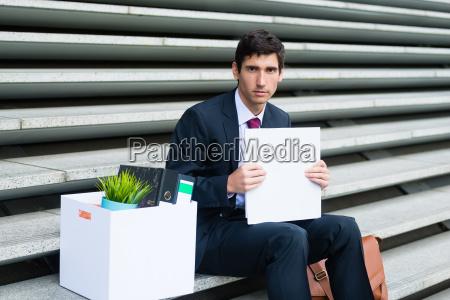 junger arbeitsloser mann sitzt auf der