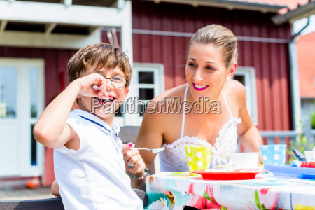 mother with son eating fruit cake