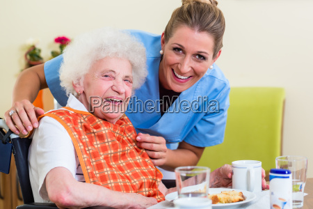 nurse with senior woman helping with