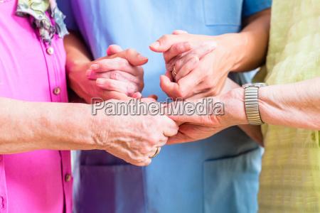 elderly care nurse with two senior