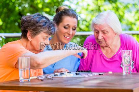 two senior ladies playing board game