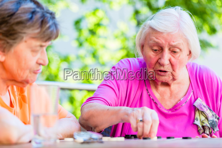 two senior ladies playing board game