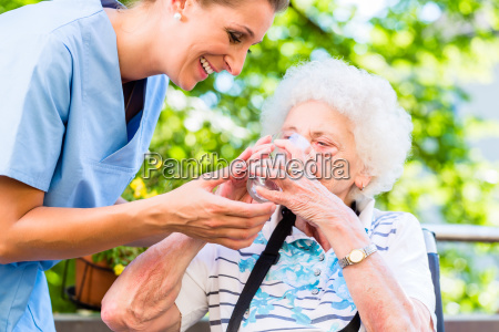geriatric nurse giving glass of water