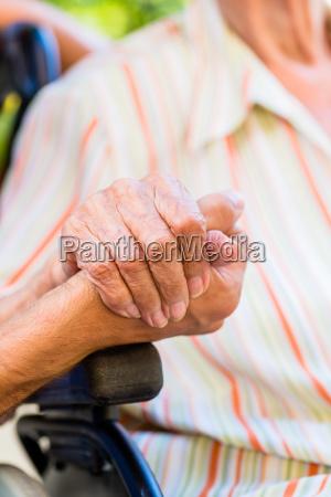 nurse holding hand of senior woman