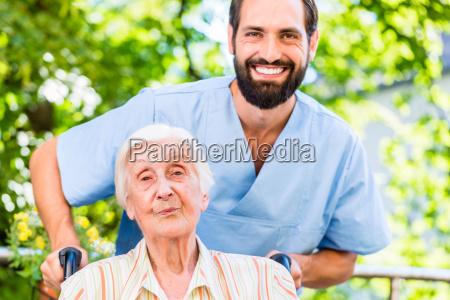 geriatric nurse pushing senior lady in