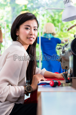 asian tailor woman sewing dress with