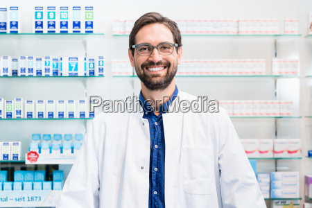 apothecary in pharmacy standing at shelf