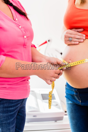standing pregnant women and midwife measuring