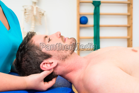 physiotherapist woman treating young bare chested