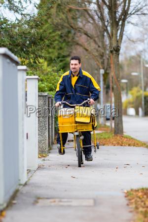 postman riding his cargo bike carrying