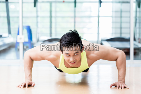 muscular asian man doing pushups in