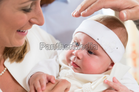 mother baby and priests hand at