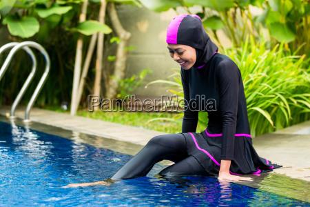 muslim woman wearing burkini swimwear at
